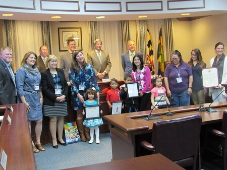 Commissioner Tom Hejl; Tracy Loyd and Celia Engel of HIPPY/Healthy Families; Erica Durner (Age 3 winner) and Home Visitor Jacky Montague; Erick Masrukin (Age 4 winner), EduardoMartinez-Cruz (age 5 winner) and Home Visitor Dalys Innocenti; Camille Arias (Age 5 winner) and Home Visitor Anne Gerlach Anjelica Eitel of United Way of Calvert County; Jennifer Moreland of Calvert County Family Network